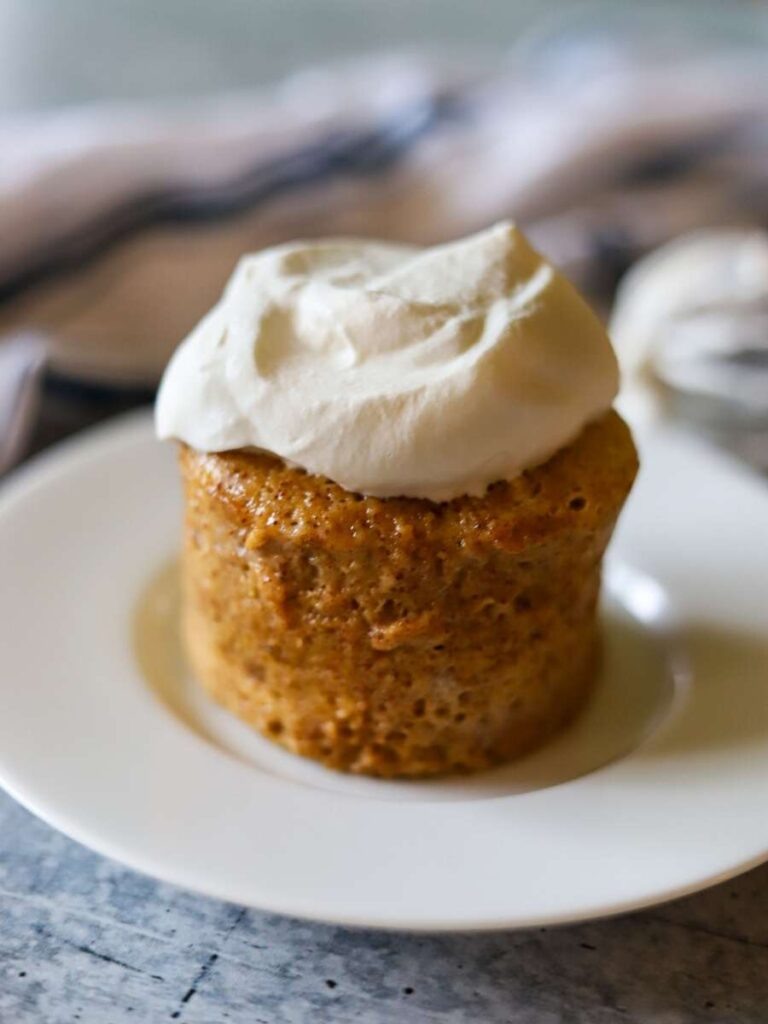An almond butter mug cake on a white plate topped with fresh whipped cream