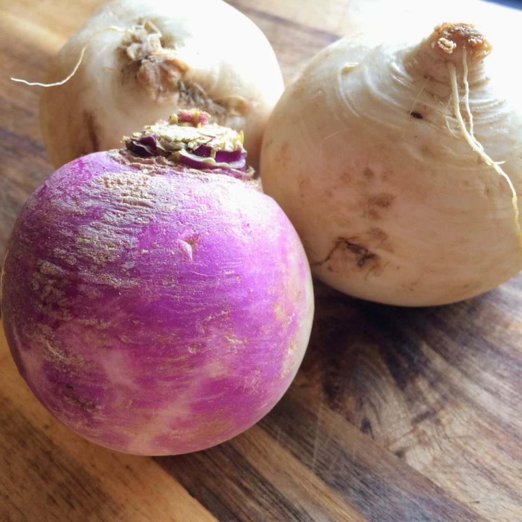 3 small turnips, one purple and 2 white, on a wooden cutting board