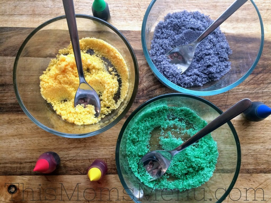 Three bowls of colored erythritol, one green, one yellow, and one purple, to decorate a keto king cake.
