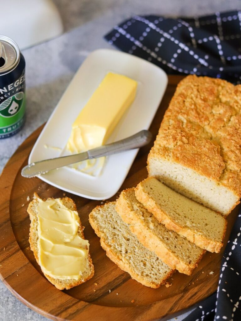 Keto bread sliced on a wooden board with a can of beer and butter in the background