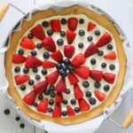 an overhead shot of a fruit pizza topped with fresh blueberries and strawberries
