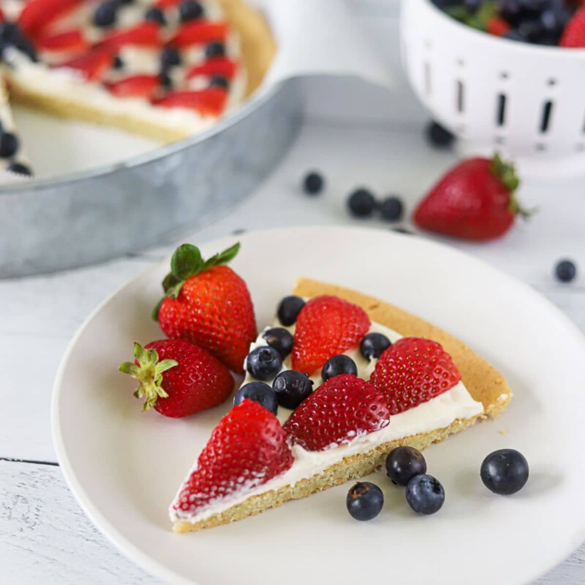 a slice of cookie pizza with cream cheese icing and berries on top.