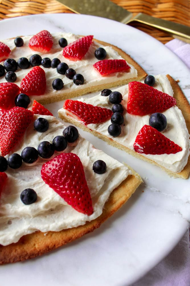 a keto fruit pizza topped with frosting and berries