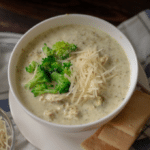 slow cooker chicken broccoli alfredo soup in a white bowl