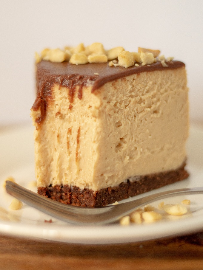 A single slice of keto chocolate peanut butter cheesecake with one bite taken