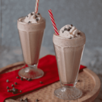 Two glasses full of keto frozen hot chocolate topped with whipped cream and chocolate chips with a red and white straw