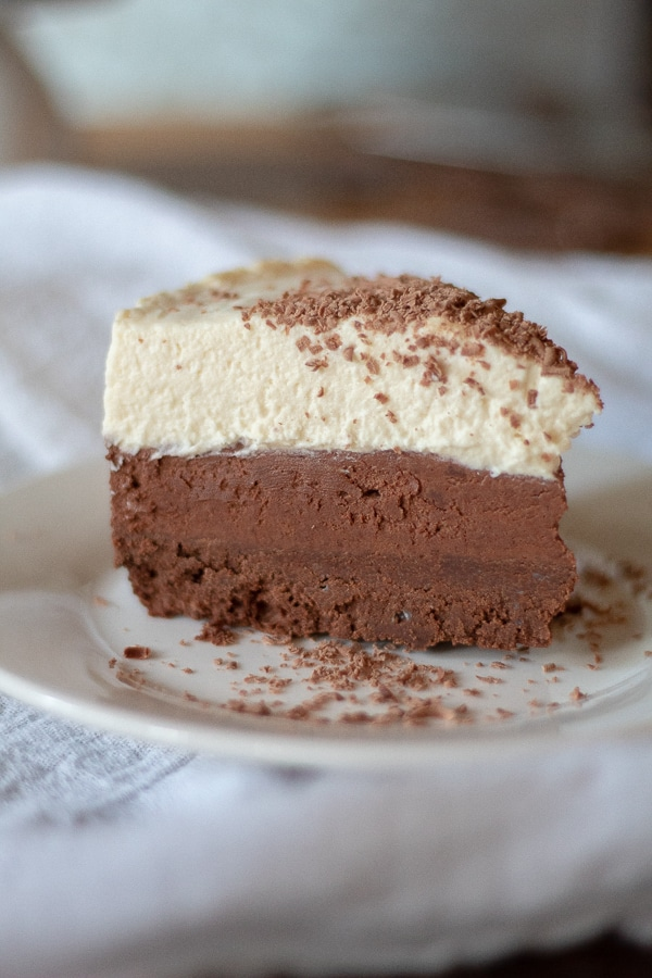 a slice of low carb mousse cake on a plate with three distinct layers, dark chocolate on the bottom, milk chocolate in the center, and white chocolate on the top.