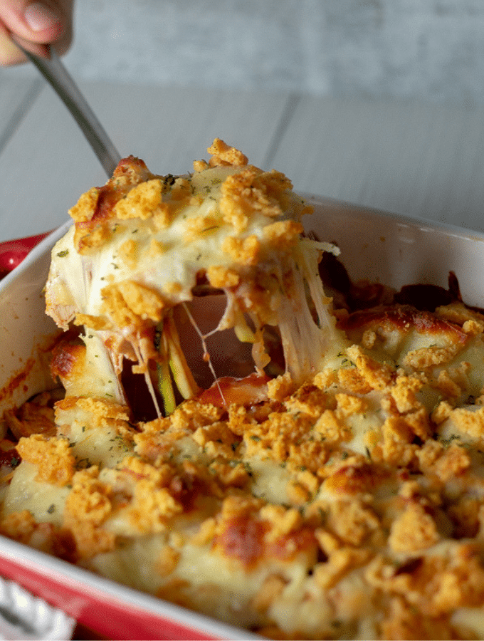 keto chicken Parmesan casserole in a red dish being served with a large silver spoon