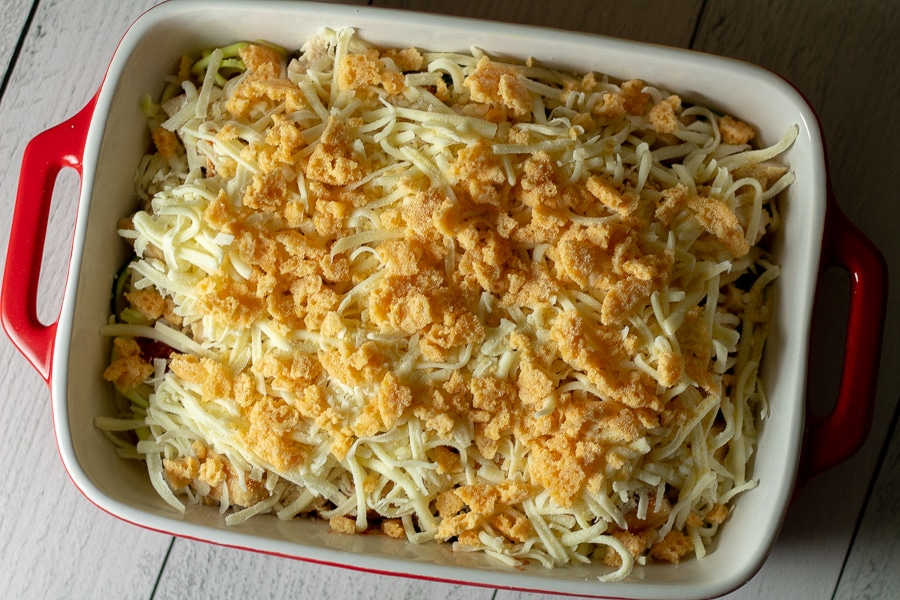 preparation of Keto Chicken Parmesan Casserole with layers of zoodles, marinara, chicken, mozzarella cheese, and Parmesan cheese crisps