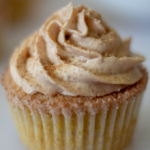 A single keto churro cupcake topped with cinnamon cream cheese frosting and a cinnamon sugar sprinkle