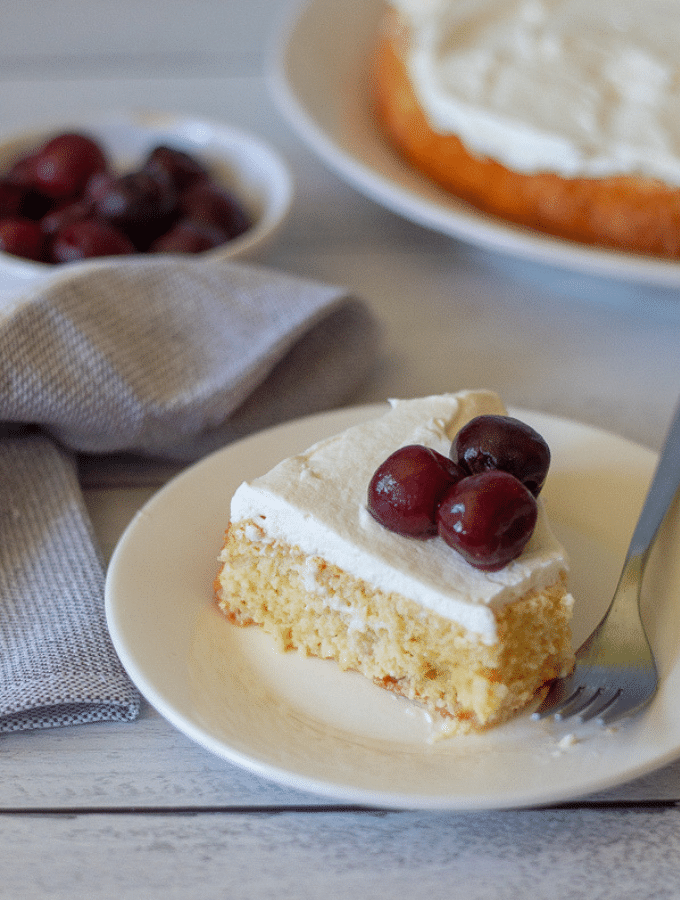 a slice of gluten free tres leches topped with fresh cherries