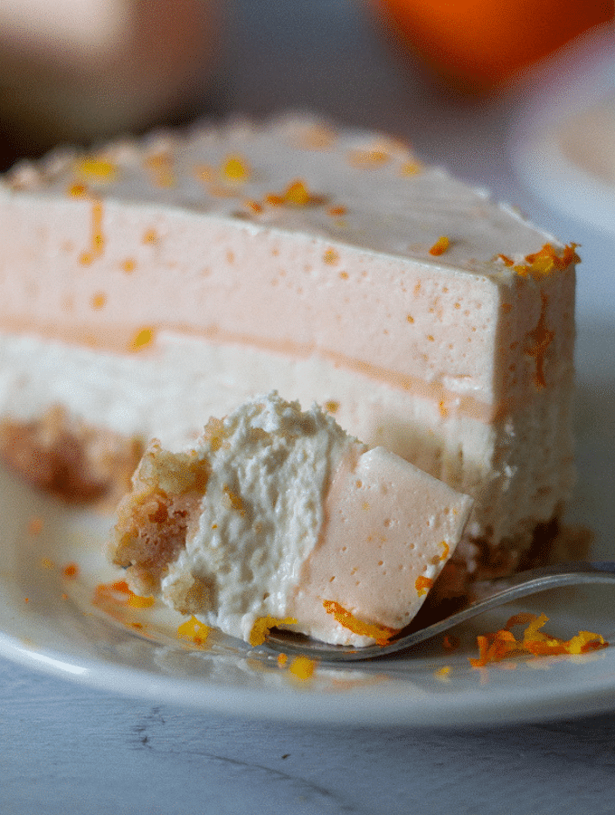 A single slice of orange cheesecake on a white plate topped with freshly grated orange zest