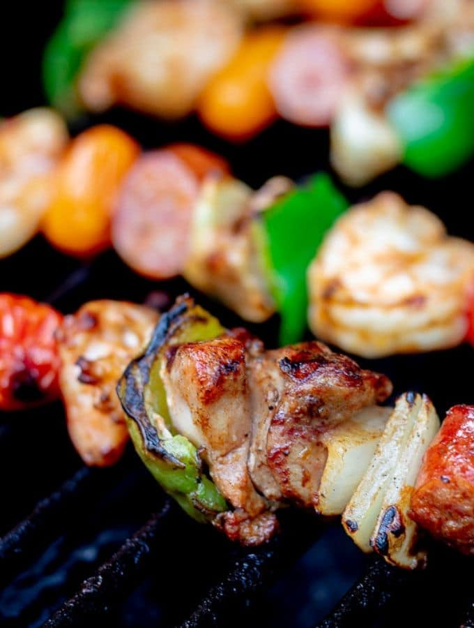 Keto kabobs with shrimp, chicken, andouille sausage, peppers, cherry tomatoes, and onions cooking on the grill