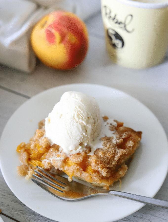 a slice of low carb peach cobbler on a white plate topped with vanilla ice cream
