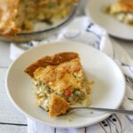 A slice of keto chicken pot pie on a white plate with peas, carrots and turnips spilling out of the pie.