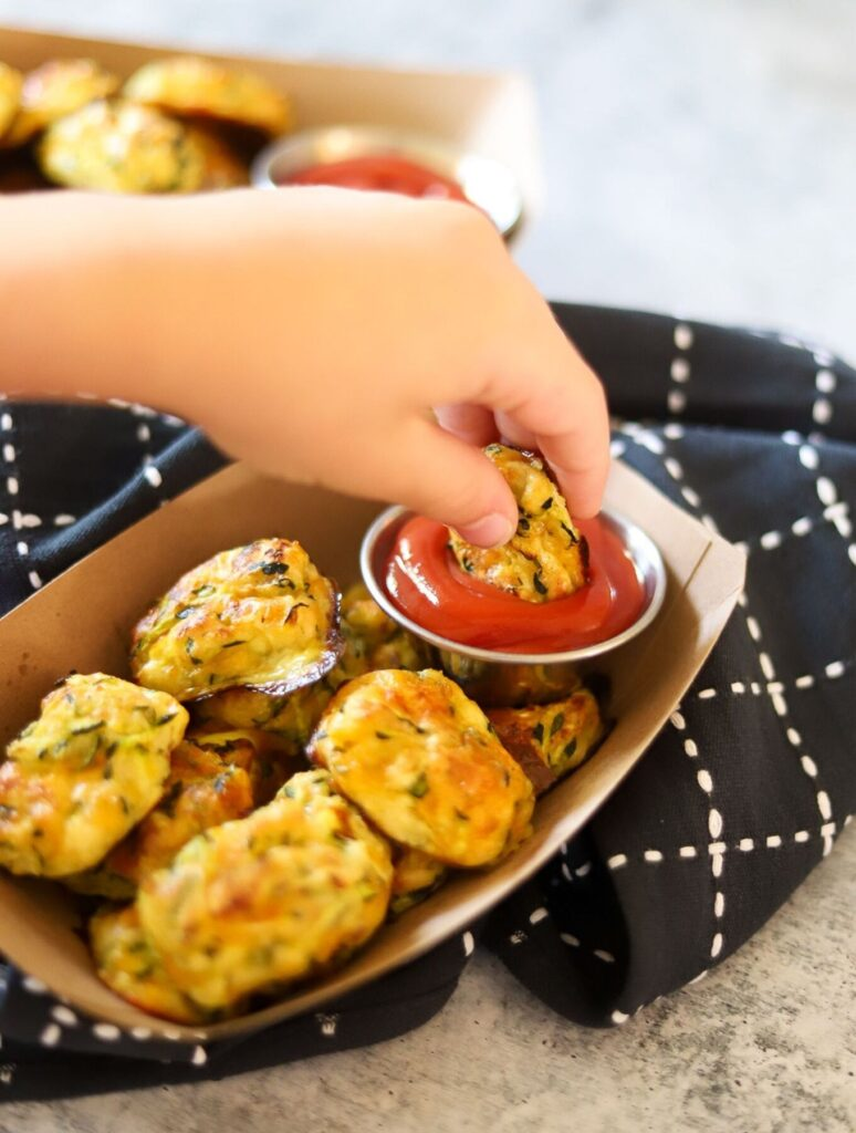 A child's hand dipping a zucchini tot in ketchup