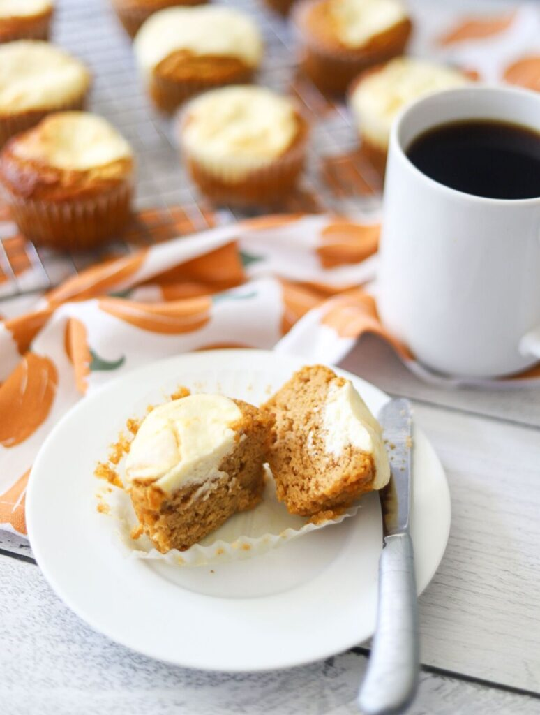 a keto pumpkin cream cheese muffin sliced in half, sitting on a white plate with a cup of coffee in the background