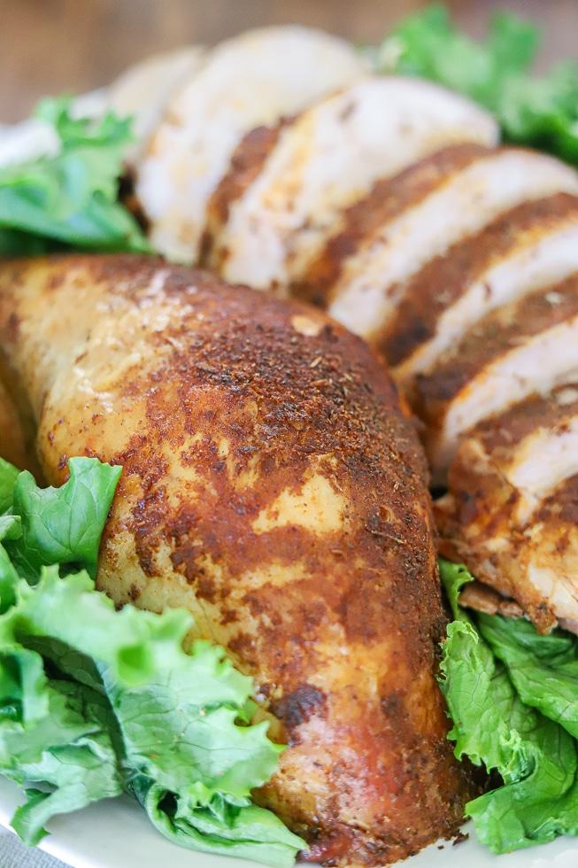 sliced turkey breast coated in seasoning on a plate of green lettuce