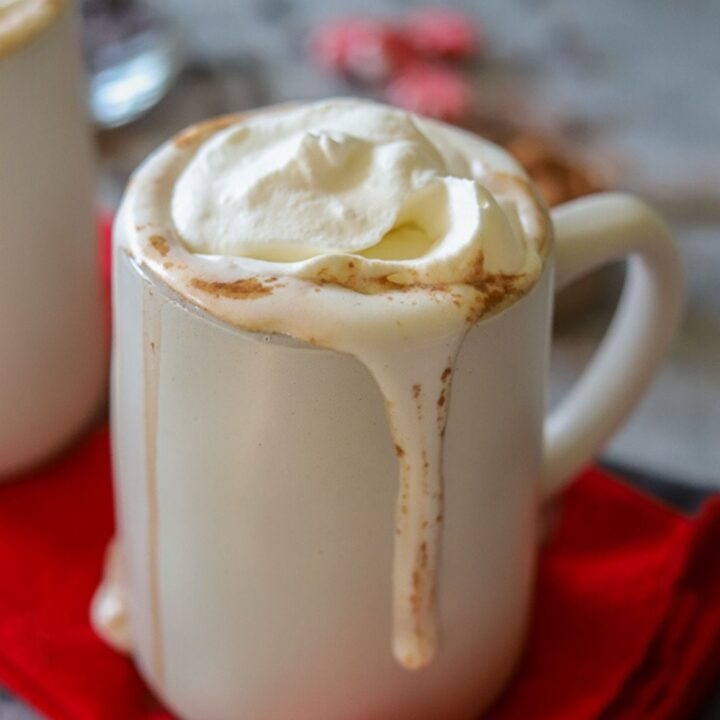 a clay mug overflowing with sugar free hot chocolate and fresh whipped cream