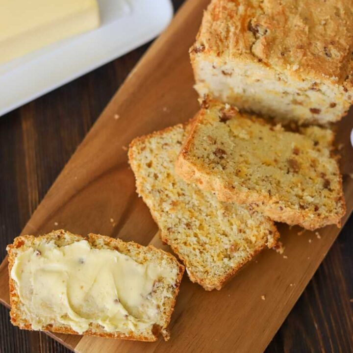 slices of savory keto bread on a woodes cutting board with one sliced spread with butter