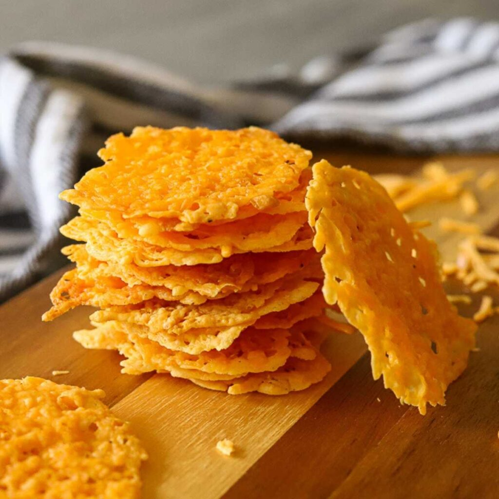 a stack of cheddar crisps on a wooden serving tray
