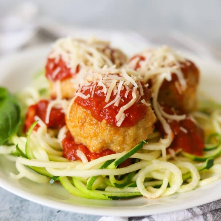 Chicken parmesan meatballs over a bed of zucchini noodles and topped with marinara and cheese