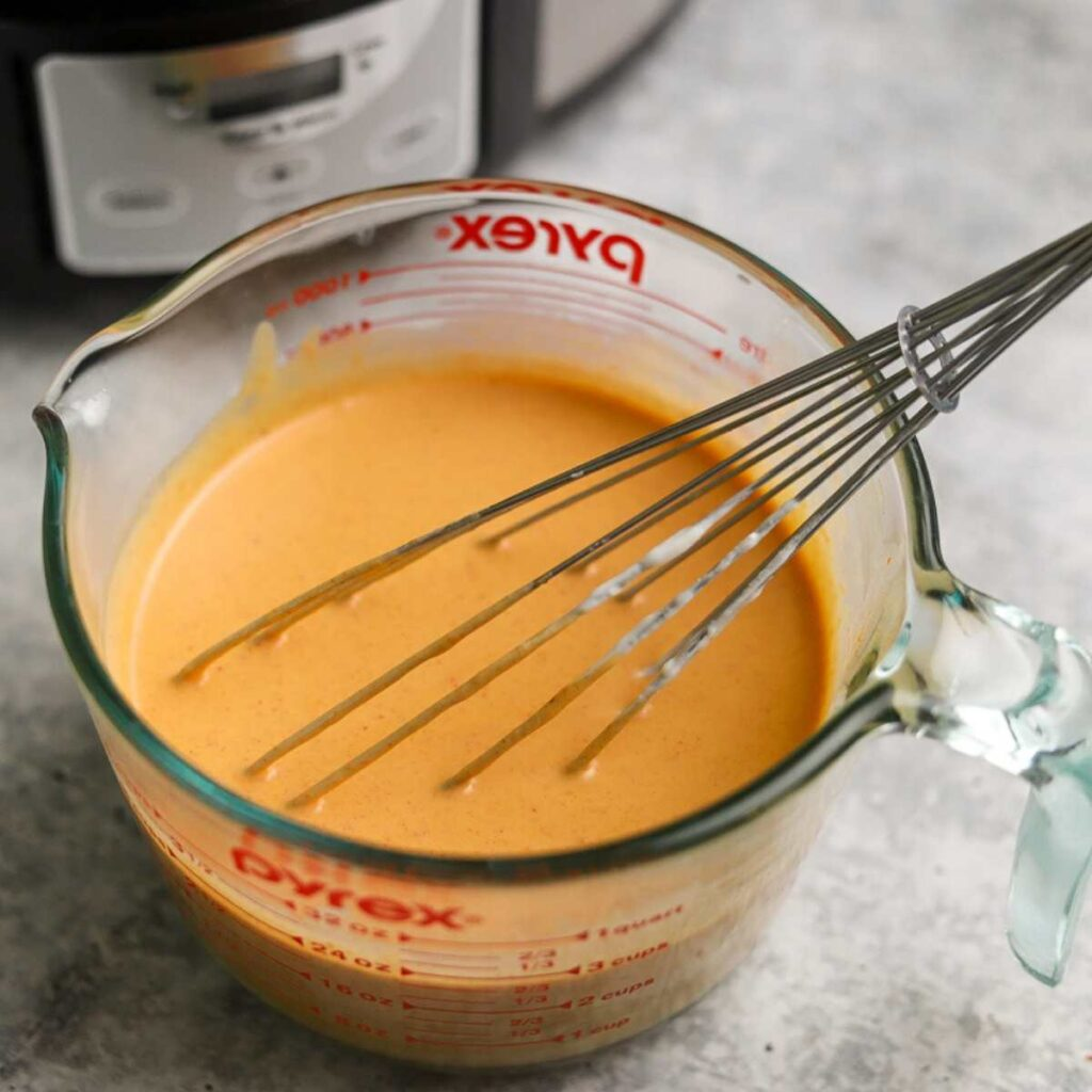 Thai peanut curry sauce in a glass measuring cup