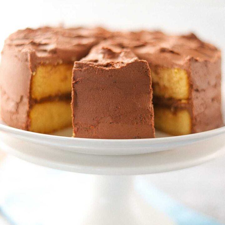 A yellow cake with chocolate frosting on a white cake stand with two slices removed