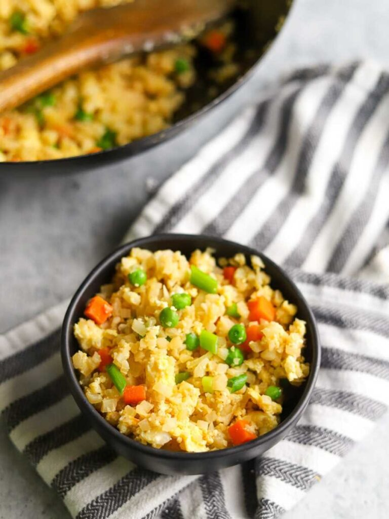 a bowl of cauliflower fried rice with a wok in the background