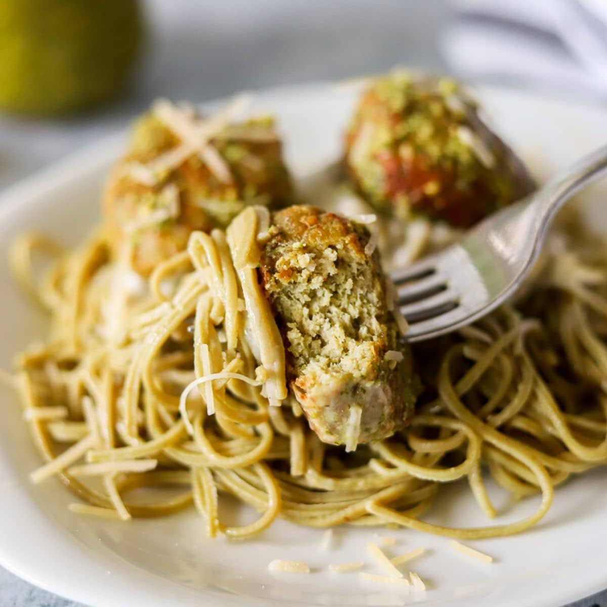a plate of pasta and meatballs. one meatball is being speared with a fork and a bite has been taken.