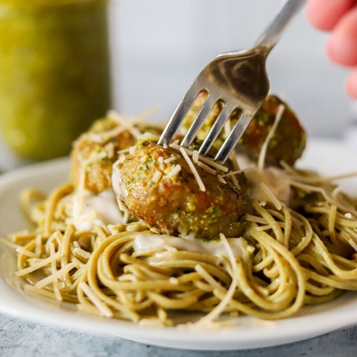 edamame pasta on a white plate toped with alfredo sauce and chicken pesto meatballs.