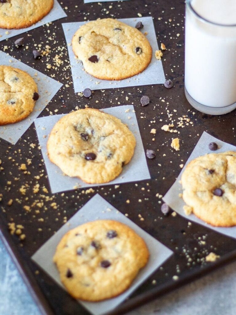 gluten free chocolate chip cookies on individual parchment squares, with scatted crumbs and chocolate chips plus a glass of almond milk off to the side.