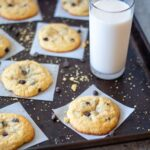 chocolate chip cookies on individual parchment squares, with scatted crumbs and chocolate chips plus a glass of milk off to the side.