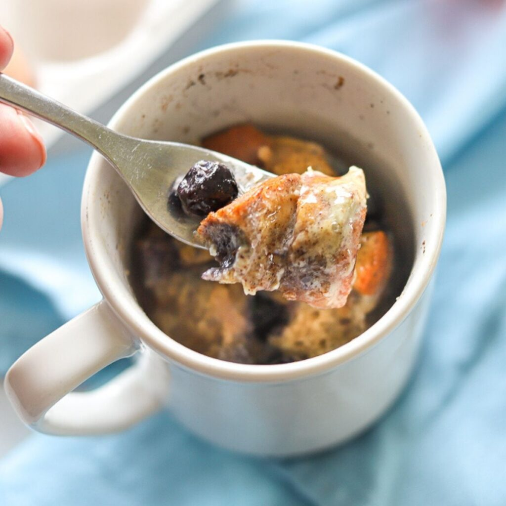 french toast in a mug with one bite being taken. The french toast is topped with blueberries and syrup.
