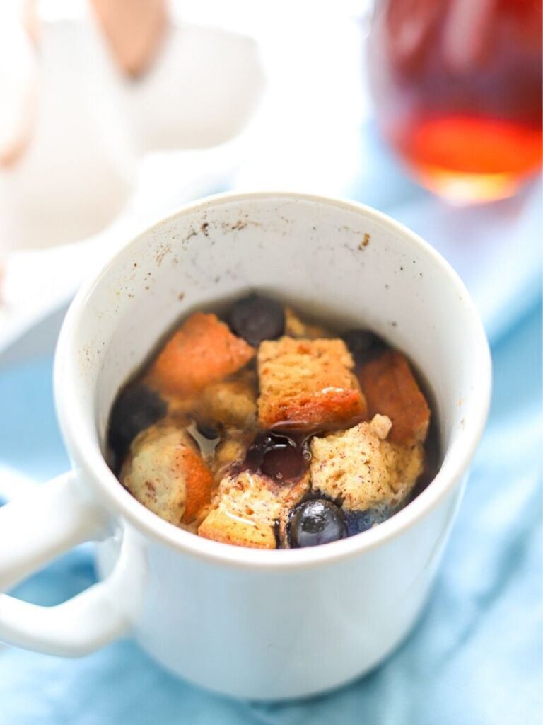 A white coffee mug full of french toast with blueberries