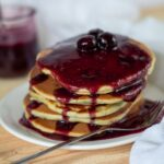 A stack of keto blueberry pancakes topped with a blueberry sauce