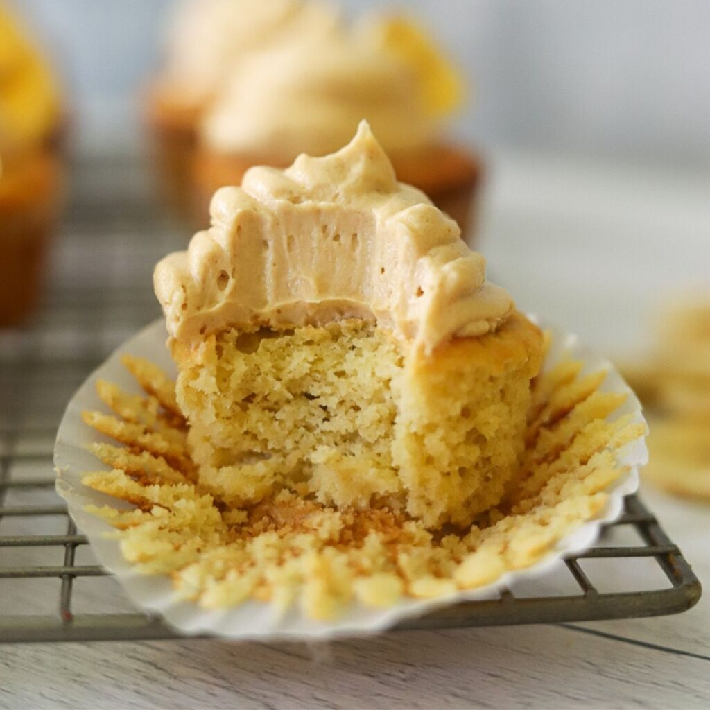 a single gluten free banana cupcake topped with peanut butter frosting. One bite has been taken from the cupcake.