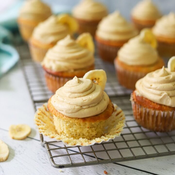 gluten free banana cupcakes on a wire cooling rack. The cupcakes are topped with peanut butter frosting and a single banana chip on each cupcake.