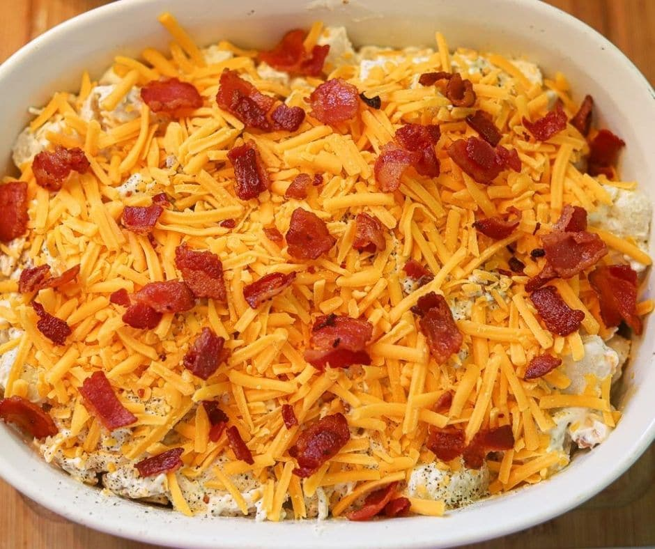 an overhead image of a loaded cauliflower casserole topped with cheese and bacon being prepared to bake.