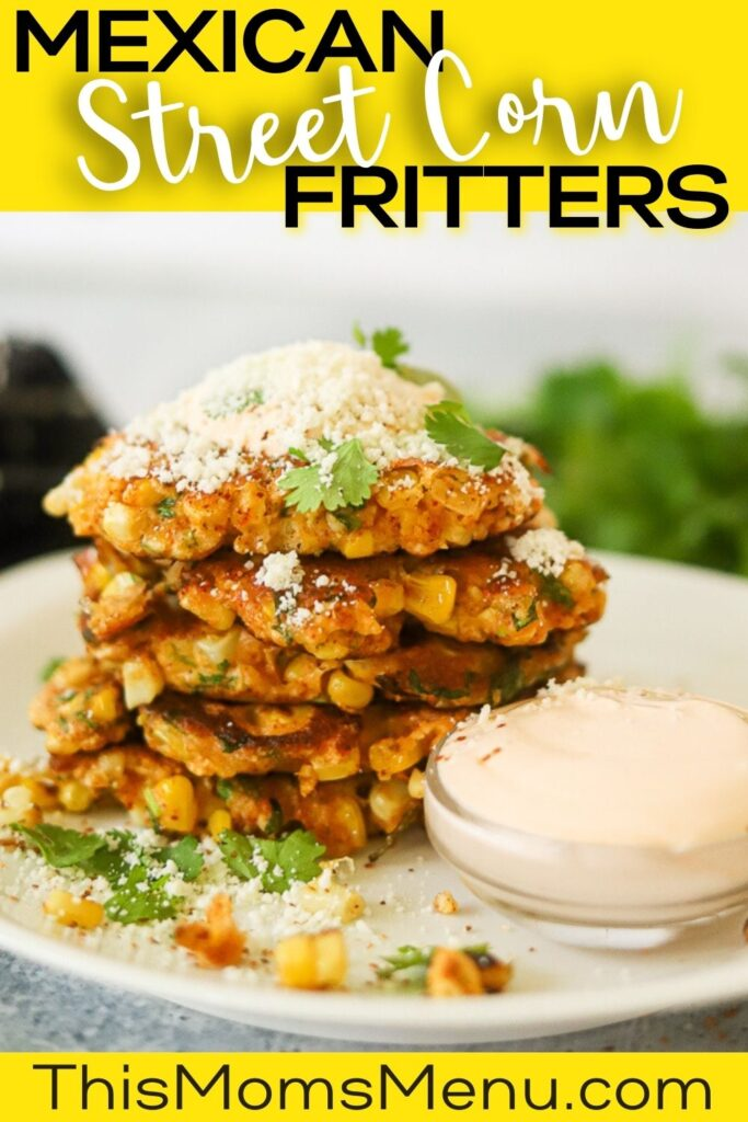 A stack of elote corn fritters on a white plate topped with sour cream and cotija cheese.
