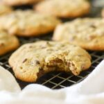 a wire cooling rack with chocolate bourbon pecan cookies. One cookie has a bite taken