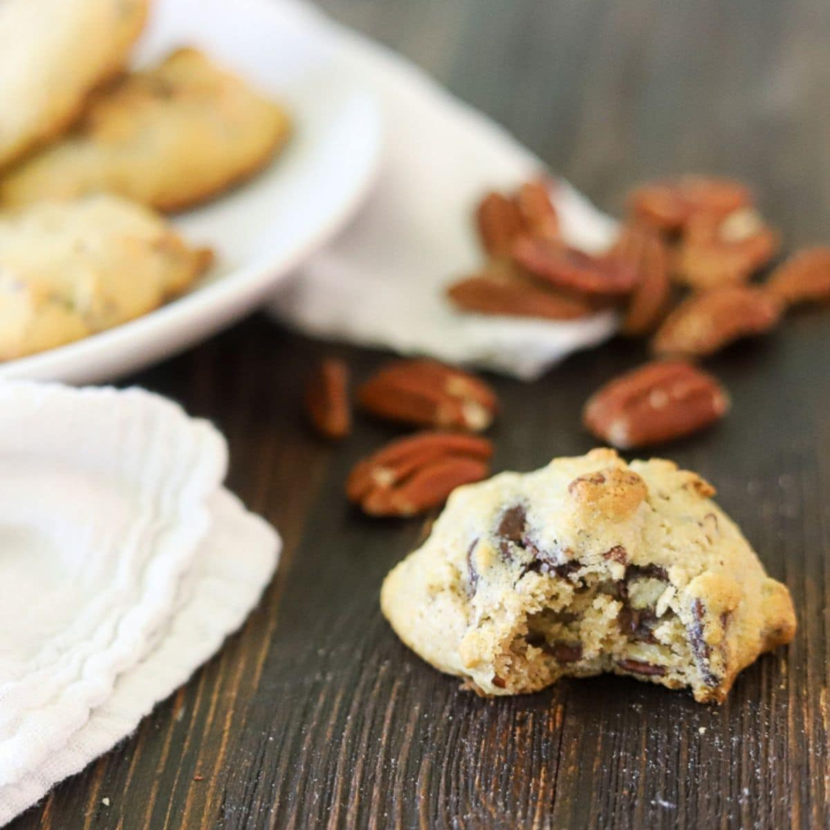 low carb derby cookie on a wooden board surrounded by pecan halves.