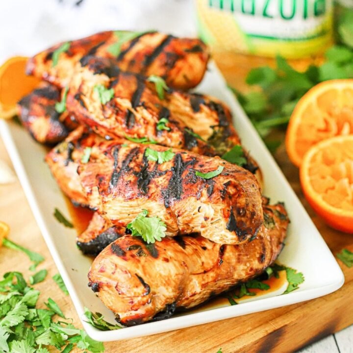 a white platter piled with grilled chicken breast and topped with chopped cilantro