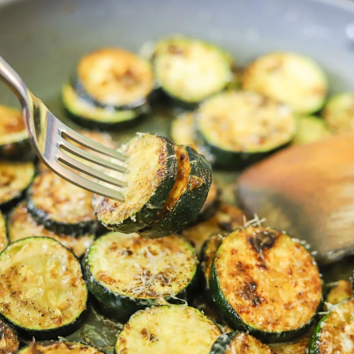 Garlic and Parmesan Sauteed Zucchini being picked up from the skillet with a silver fork