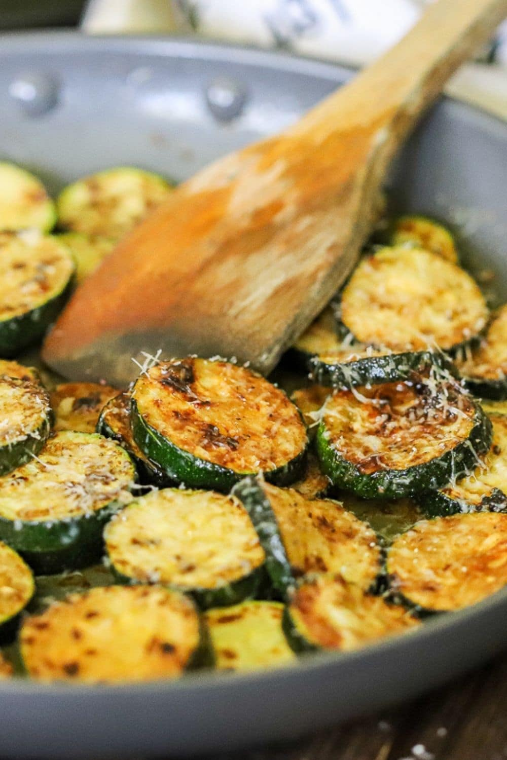 browned zucchini topped with thinly shedded parmesan cheese in a skillet with a wooden spoon.