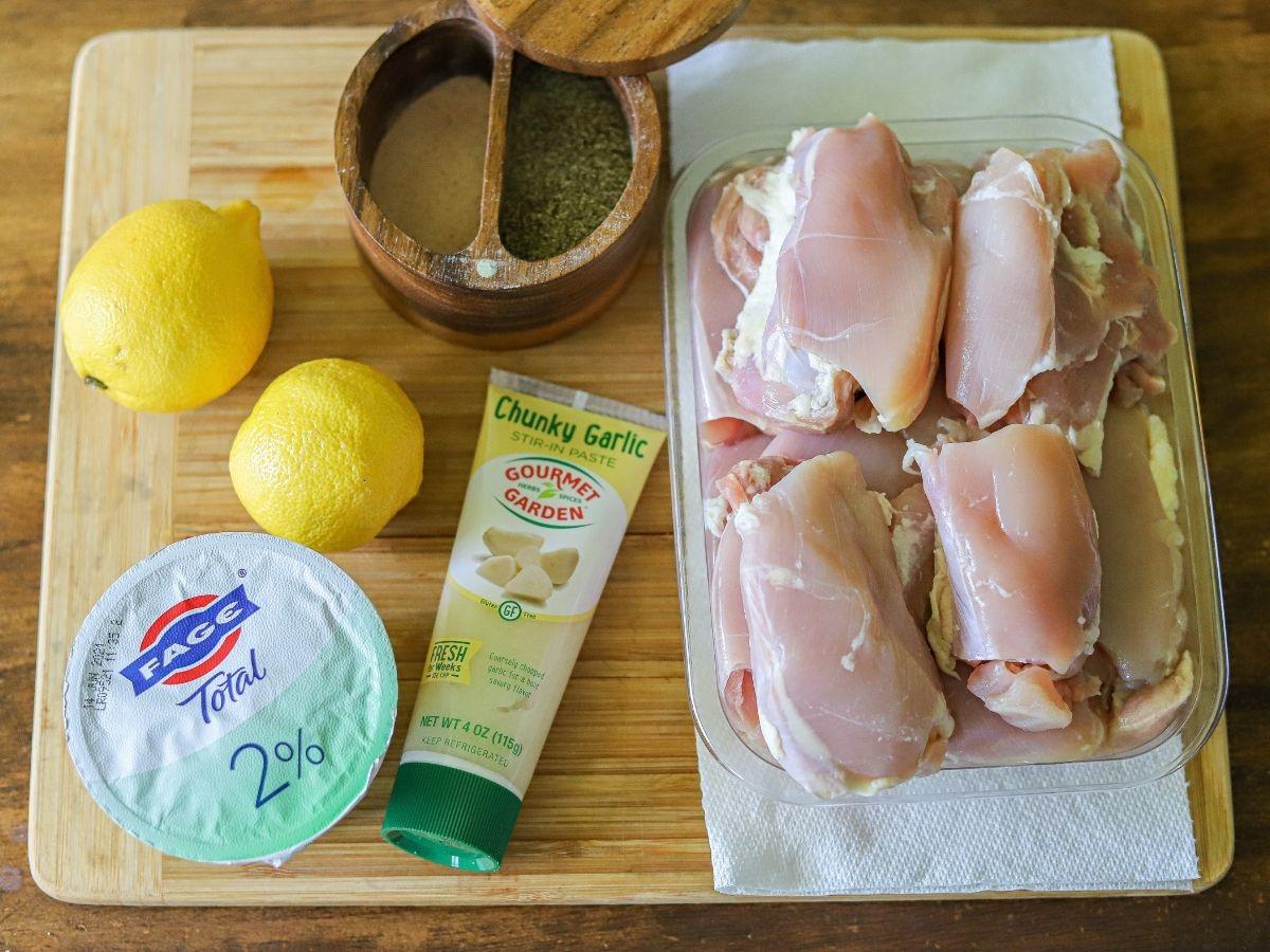 Boneless skinless chicken thighs, garlic, lemons, plain greek yogurt, salt and pepper on a cutting board.