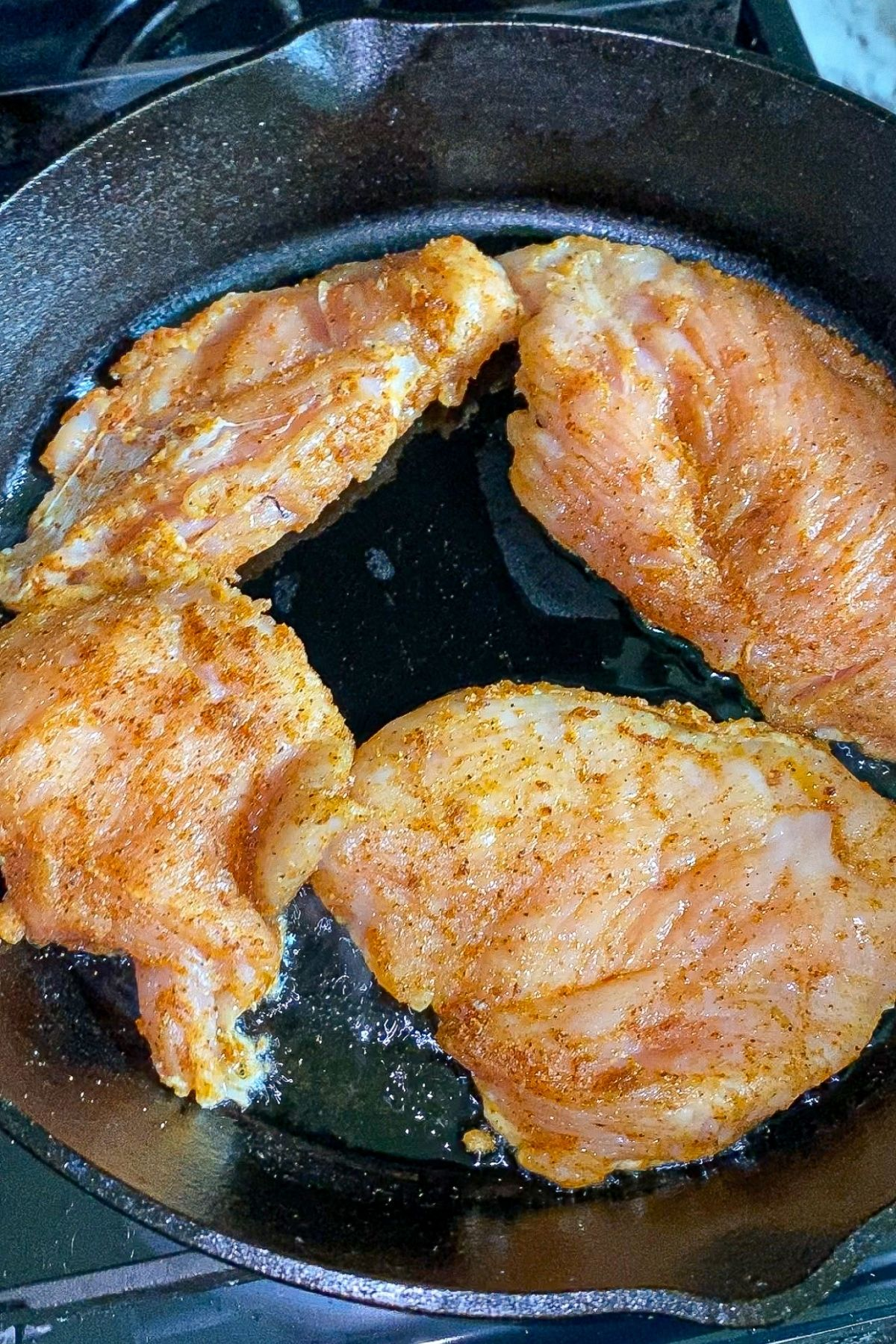 chicken breast coated in Mexican spices , cooking in a cast iron skillet.
