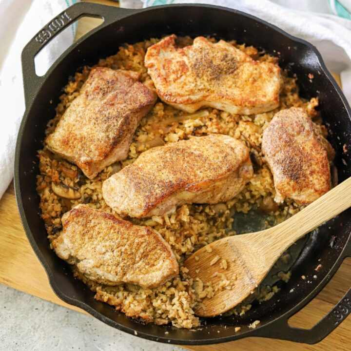 a cast iron skillet full of cauliflower rice topped with pork chops. A wooden spoon os resting on the side.