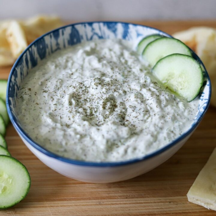 homemade Tzatziki sauce in a bowl with cucumber slices for dipping