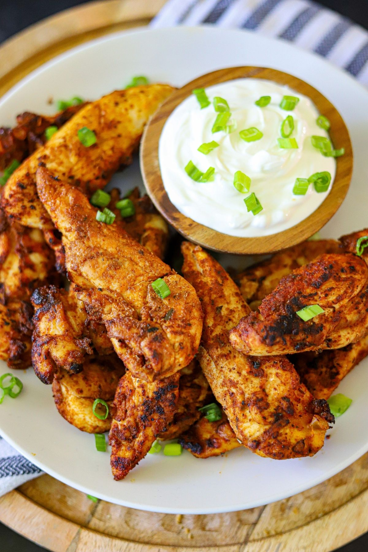 A plate full of chicken tenders cooked with blackening spice and garnished with sliced green onions and a dollop of sour cream.